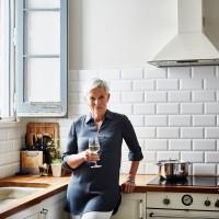Portrait of confident senior woman holding wineglass in kitchen